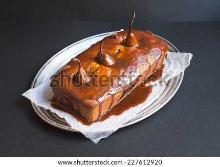 Spicy pear cake with caramel topping on a silver dish on a dark background - stock photo