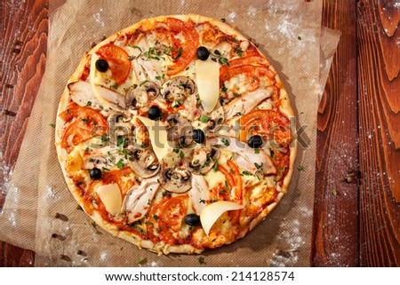 Spicy Pizza with Mozzarella, Chicken Breast, Tomatoes and Black Olives - stock photo