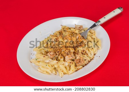 Spicy plate of blackened chicken and pasta with creamy Alfredo Sauce and sprinkled with Cajun Spices.  White plate on red tablecloth.  Horizontal format with copy space. - stock photo
