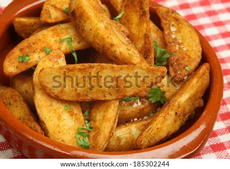 Spicy potato wedges in terracotta dish. - stock photo