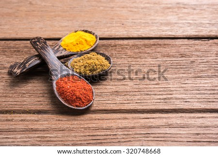 spicy powder spoon on the wooden table - stock photo