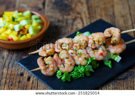Spicy prawns on skewers with mango salsa - stock photo