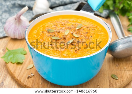 spicy pumpkin soup with coriander in a saucepan, close-up - stock photo