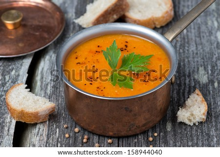 Spicy red lentil soup in a copper pot on a wooden table, close-up