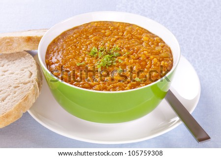 Spicy red lentil soup with parsley and bread, in a green bowl. - stock photo