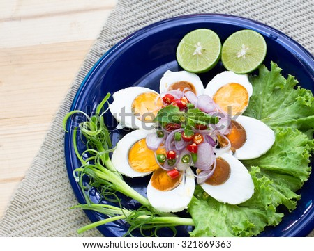 Spicy salad with salted eggs on blue dish, Thai food