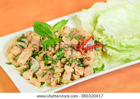 Spicy salmon salad in Thai style on orange background