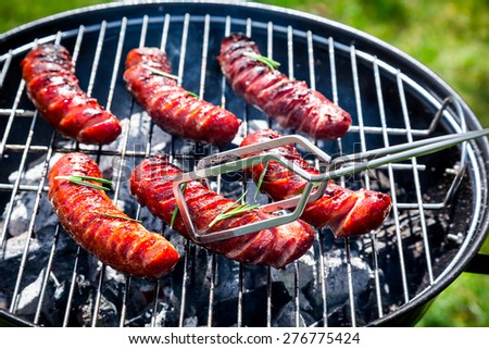 Spicy sausages with spices and rosemary on a grill - stock photo