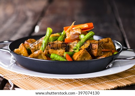 Spicy snack of fresh roast vegetables and tofu in a bowl on a rustic dark brown wooden table - stock photo