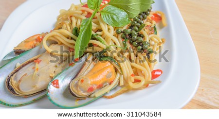 Spicy spaghetti Stir-fried with New Zea-land mussels on white dish - stock photo