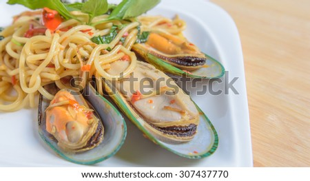 Spicy spaghetti Stir-fried with New Zealand mussels on white dish - stock photo