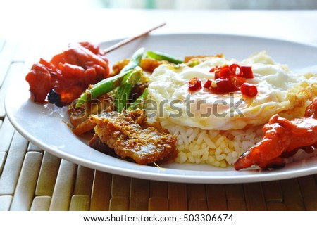 spicy stir fried crispy pork curry with egg and grilled pork stick