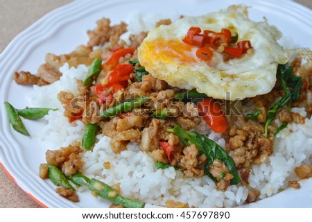 spicy stir fried minced pork with basil leaf topping egg on rice