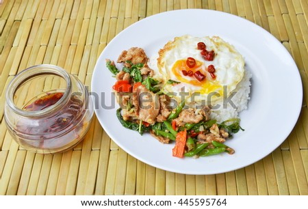 spicy stir fried pork with basil leaf and egg on rice