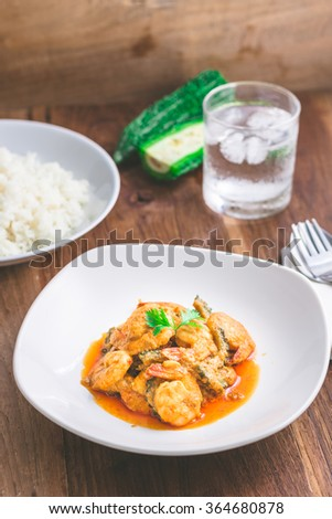 Spicy Thai food. Delicious red curry with gourd and shrimp on dish on wooded table - stock photo