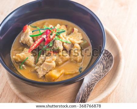 Spicy Thai food. Delicious red curry with pork and pumpkin on black bowl. Warm light tone - stock photo