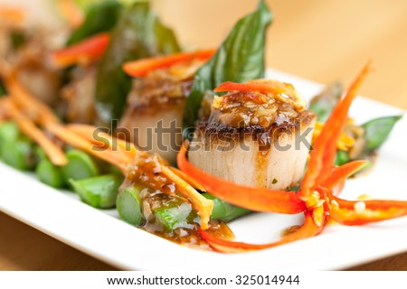 Spicy thai scallops on a bed of asparagus spears. - stock photo