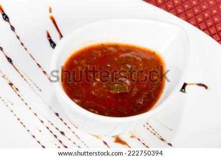 spicy tomato sauce in a gravy boat white - stock photo