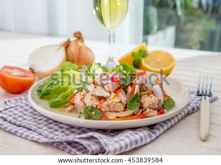 Spicy Tuna Salad onion and tomatoes in plate put on tabal , Thailand cuisine. - stock photo