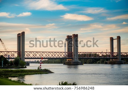 SPIJKENISSE, NETHERLANDS - JULY 30, 2017 A beautiful red oud bridge, river Old Maas and ship with containers in Spijkenisse in Holland