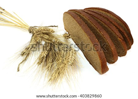 Spikelets and slices of fresh rye bread - stock photo