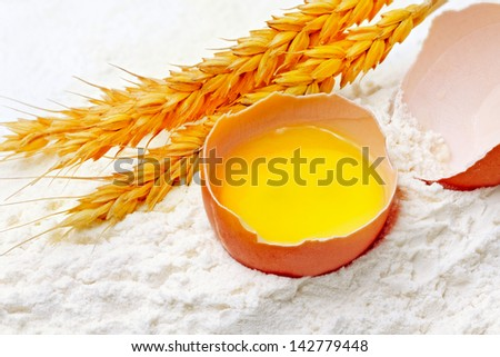 Spikelets of wheat with egg on flour spillage.Isolated - stock photo