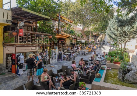 Spili, Crete, Greece - August 23, 2015: Tourists sit in summer cafe on street of Spili town at Crete island