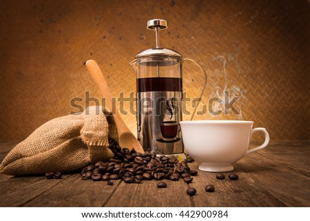 spilled coffee beans from sackcloth coffee cup coffee mug on old steel background - stock photo