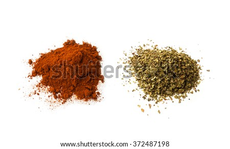 Spilled dried grounded red pepper, and dried majoram  - stock photo