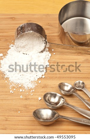 Spilled Scoop of Cooking Flour on Cutting Board - stock photo