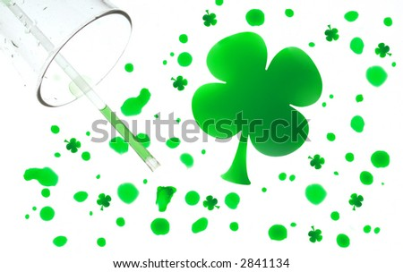 Spilled water glass with green drops shaped like four leaf clovers. - stock photo
