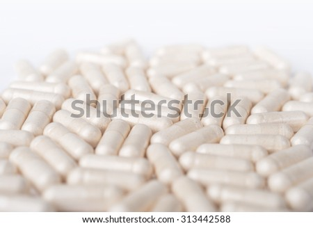Spilled white capsules on the white background - stock photo