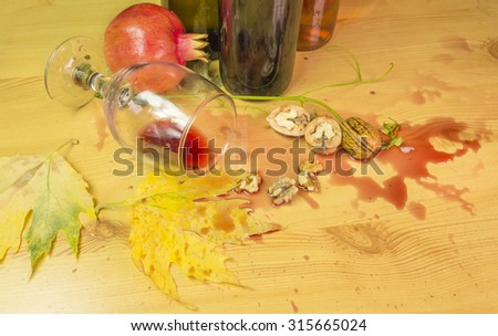 spilled wine, autumn leaves, bottles, wood - after party - stock photo