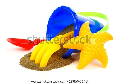 Spilling toy sand pail with rake, shovel and starfish over a white background - stock photo