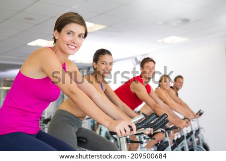 Spin class working out and smiling at camera at the gym - stock photo
