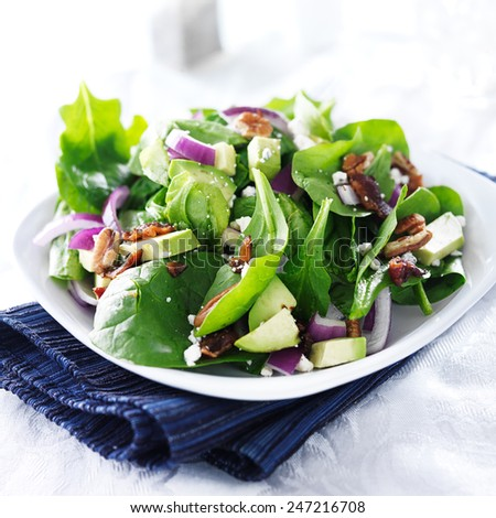 spinach and avocado salad on white plate - stock photo