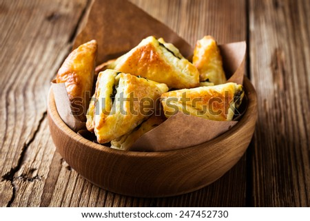 Spinach and cheese puff pastries triangles in wooden bowl - stock photo