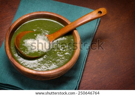 Spinach and cheese soup in a wooden bowl - stock photo