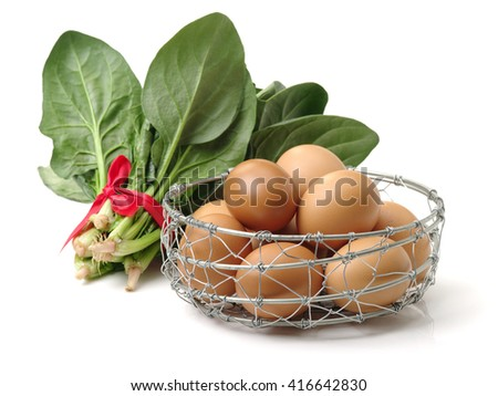 Spinach and eggs on a white background - stock photo