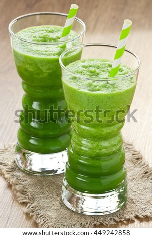 Spinach and green apple smoothie in two glass with straw on wooden background/Green spinach smoothie