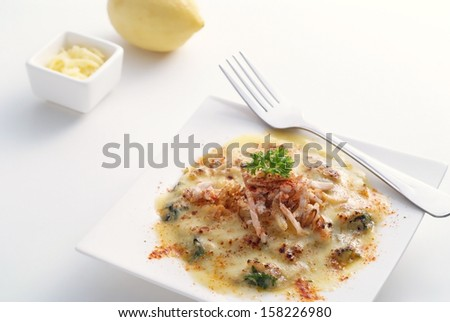 Spinach and seafood baked with cheese on white background