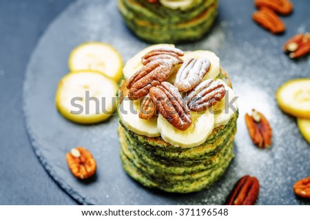 Spinach banana pancakes with pecans on a black background. toning. selective Focus - stock photo