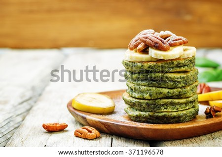 Spinach banana pancakes with pecans on a wood background. toning. selective Focus - stock photo