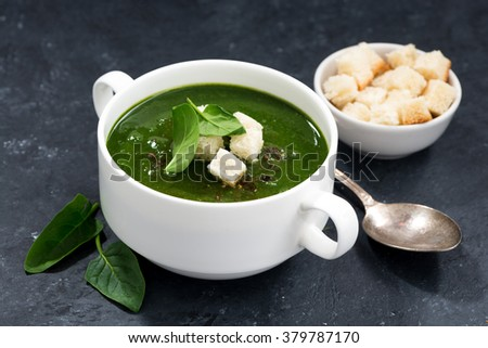 spinach cream soup with croutons on a dark background, closeup - stock photo
