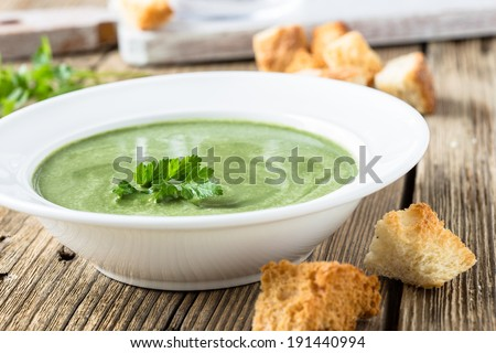 Spinach cream soup with  croutons on wooden background