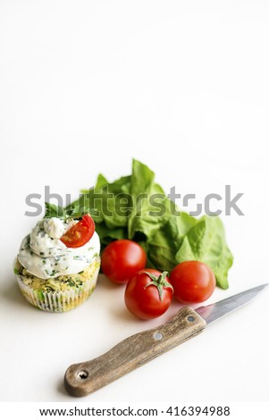 Spinach cupcakes with cream cheese frosting with fresh green onion and cherry tomatoes