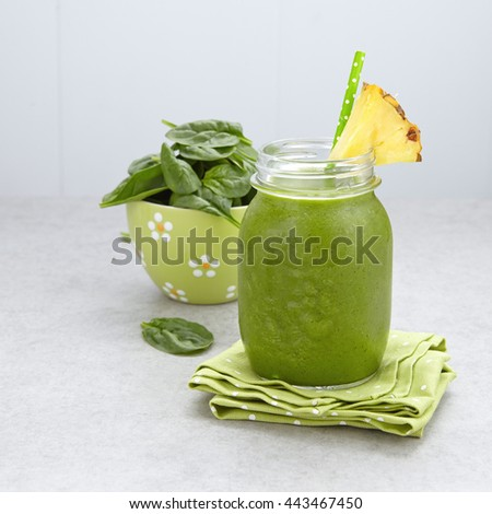 Spinach green smoothie topped with a pineapple slice - stock photo
