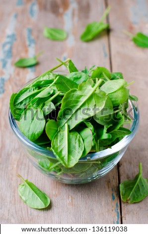 Spinach in a glass bowl on the table, selective focus - stock photo
