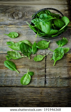 spinach in the bowl on the dark wood background. toning. selective focus on the spinach in the bowl - stock photo
