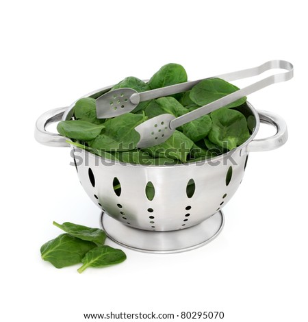 Spinach leaves in a stainless steel colander with metal tongs isolated over white background. - stock photo